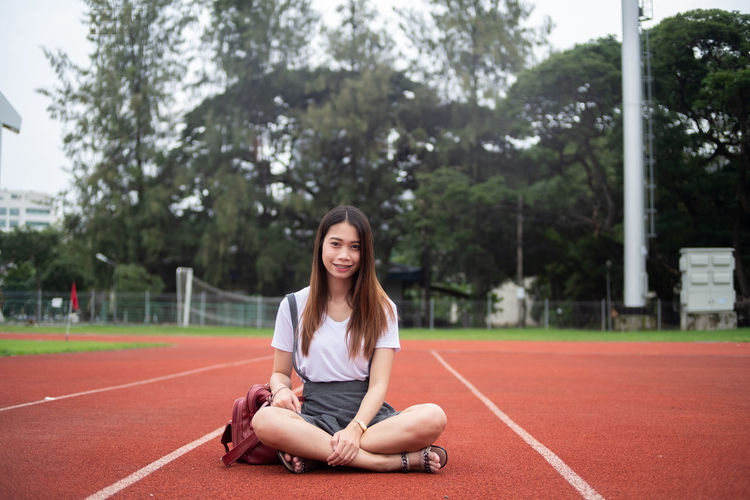 Portrait of young woman smiling while sitting on running track