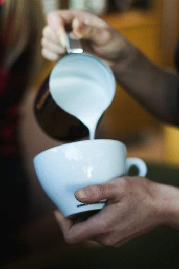 Close-Up Of Hand Pouring Milk Into Cup