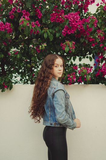 Portrait of teenager girl standing by wall with flowering plants outdoors
