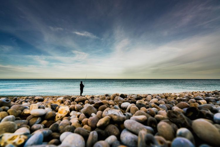 Man fishing on shore at beach