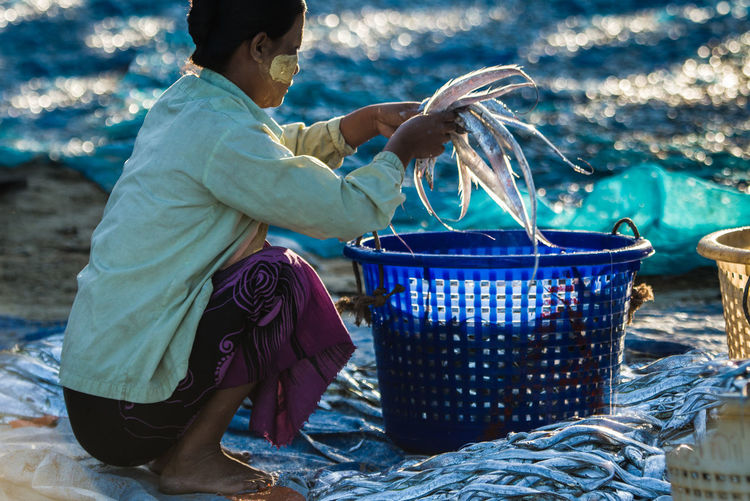 Side view of woman holding fish over basket at beach