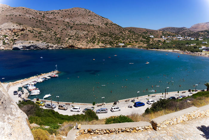 A seaside village on a Greek island . Beach Photography Bay Beauty In Nature Blue Boats Clear Sky Day Greece High Angle View Landscape Mountain Nature Outdoors People Swimming Rock - Object Seaside Village Summer Sunlight Water