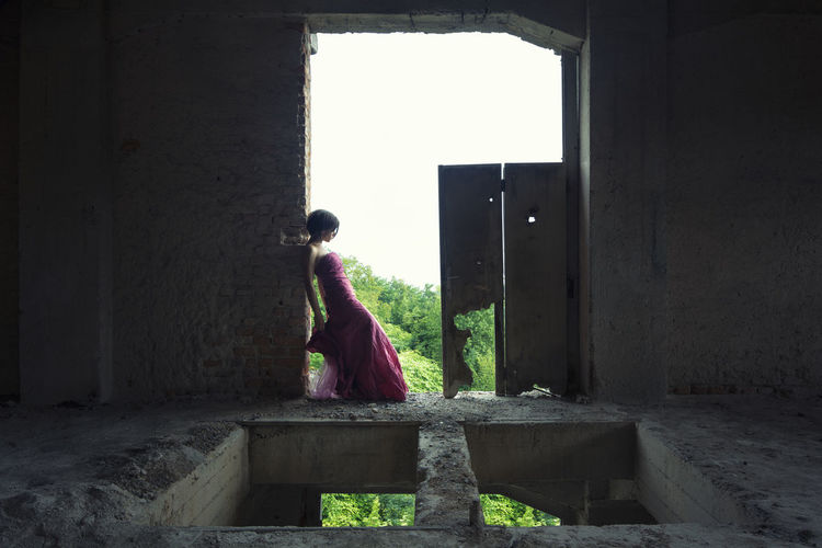 Side view of woman standing against building