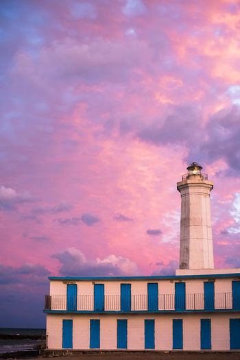 Low angle view of lighthouse by building against sky during sunset