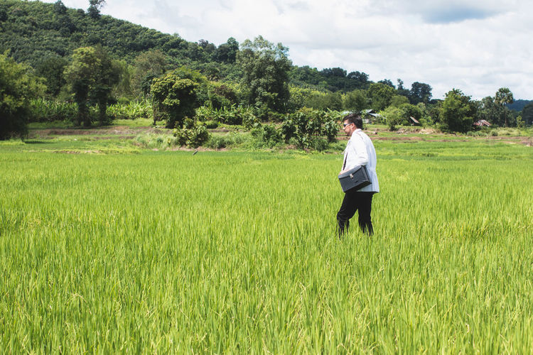 Side View Of Doctor Walking On Grassy Field Against Sky