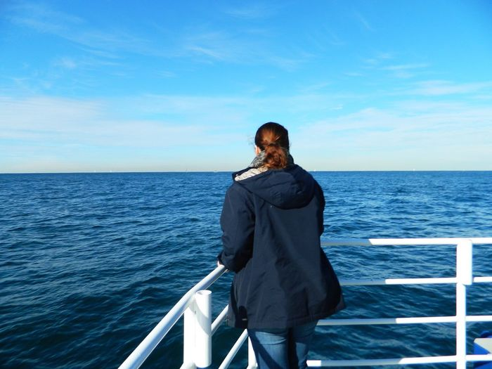 Rear view of person looking over sea against clear sky