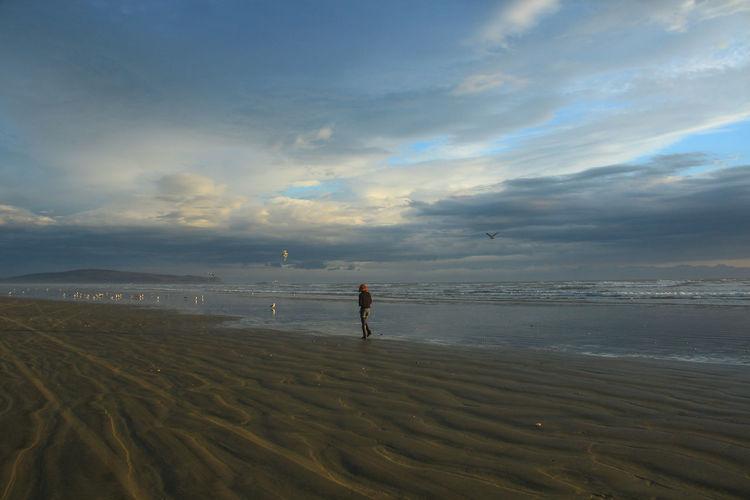Woman walking at beach during sunset