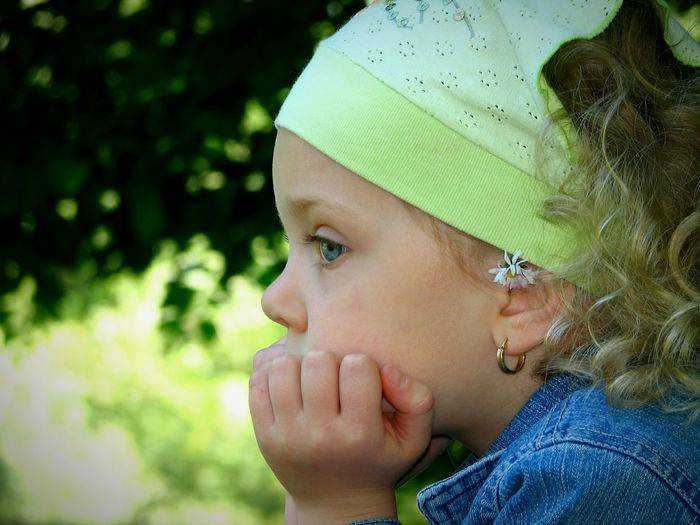 Close-Up Of Thoughtful Girl Against Trees