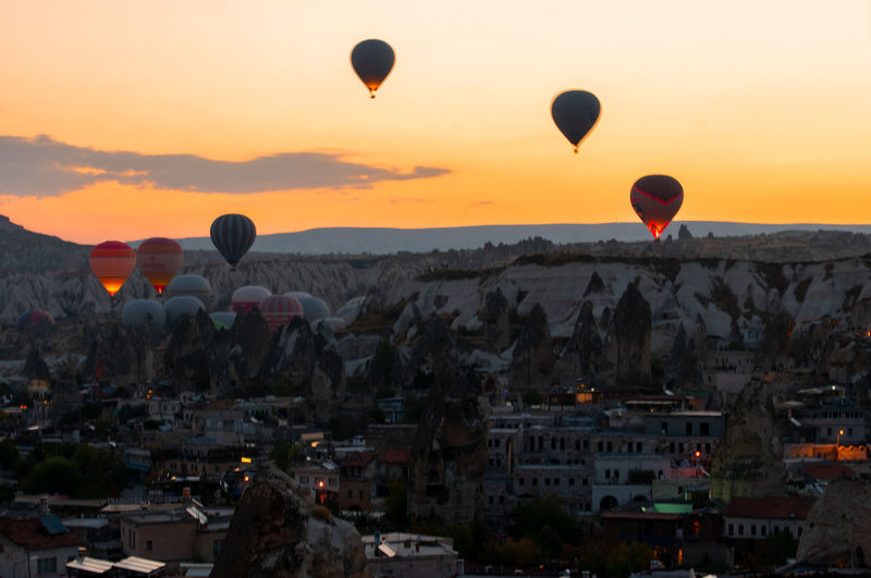 Hot air balloons flying over cityscape during sunset