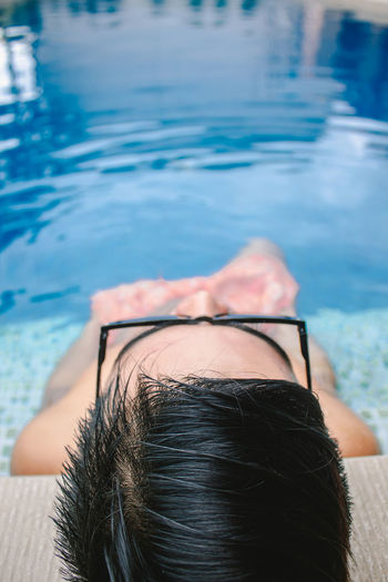 High angle view of man relaxing in swimming pool