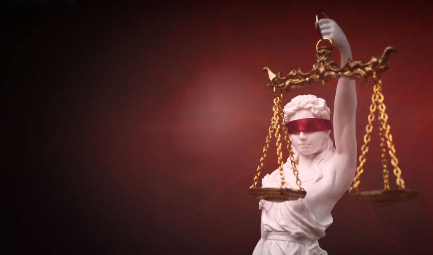 Justitia, the roman goddess of justice with red blindfold. panoramic image with copy space.