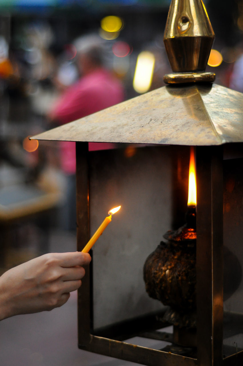 Close-Up Of Hand Lighting Oil Lamp With Candle