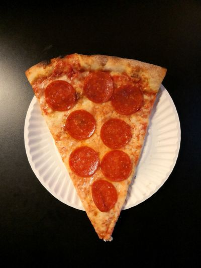Close-up of pizza on table against black background