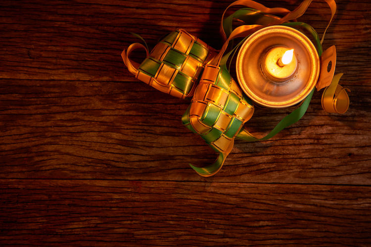 High angle view of illuminated candles on wooden table