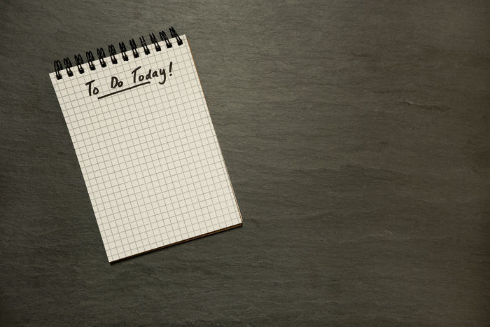 To do list on gridded spiral notepad on slate table top - from above, minimal Business Goals Grid Schedule URGENT Businesswoman Clean Dark Background Directly Above Lined Paper Minimal Note Pad Organised Page Paper Planning Day Simple Life Slate Success Table Table Top To Do List Today