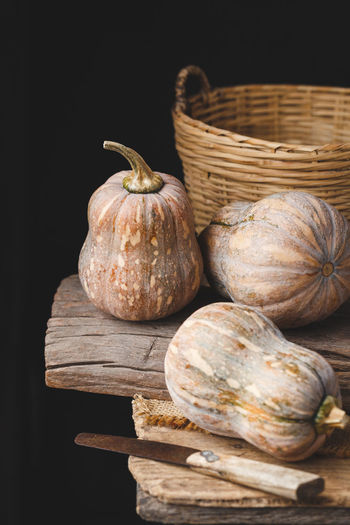 Close-Up Of Pumpkins And Basket On Table Against Black Background