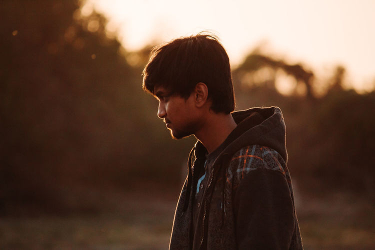 One Person Side View Child Focus On Foreground Casual Clothing Looking Nature Standing Sunset Childhood Portrait Headshot Waist Up Land Lifestyles Young Adult Contemplation Looking Away Outdoors Profile View Innocence Teenager