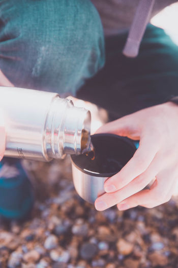 Close-up of person pouring coffee in lid