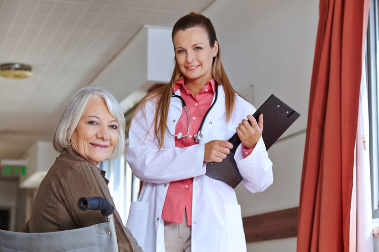 Portrait of female doctor with senior patient at hospital