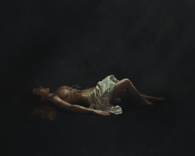 Woman lying down against black background