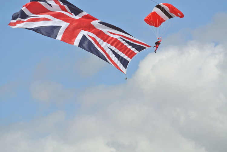 Low angle view of flag waving against sky