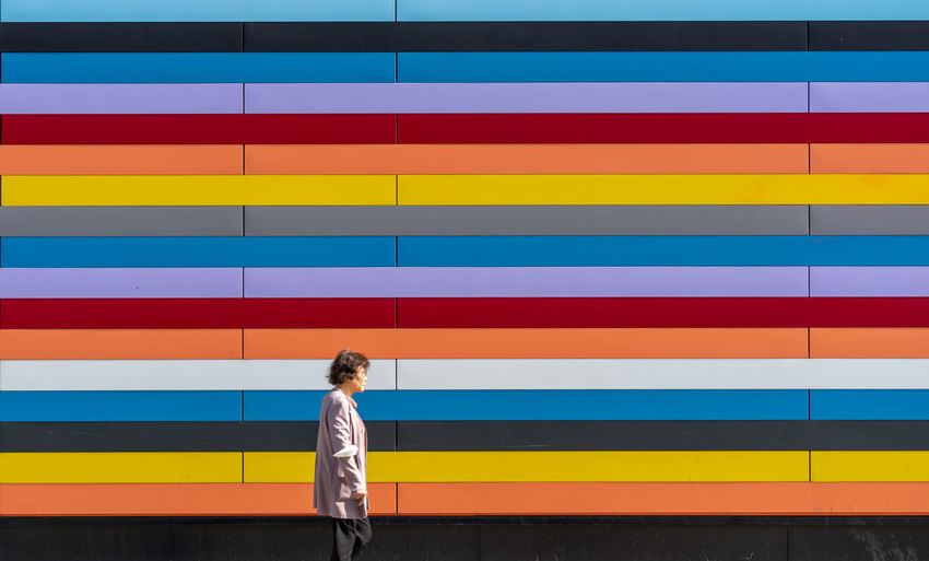 Full length of woman standing against multi colored wall