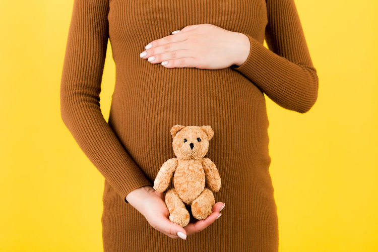 Midsection of woman holding toy against yellow background