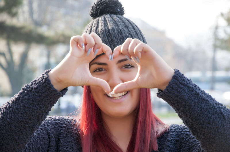 Portrait of a young attractive long haired woman with red hair and woolen hat, making a heart shape in the park Heart Shape Heart ❤ Portrait Headshot Young Adult Looking At Camera Young Women One Person Front View Real People Leisure Activity Smiling Lifestyles Happiness Emotion Winter Focus On Foreground Day Women Warm Clothing Hand Outdoors Positive Emotion Beautiful Woman