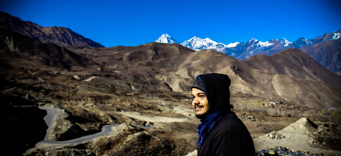 Man looking away while standing against mountains and sky