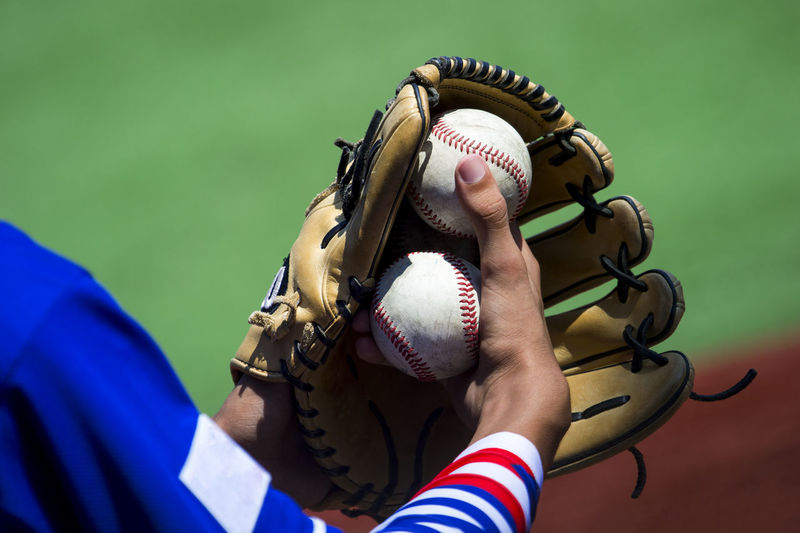 An arm stretches out to catch a baseball using a worn leather glove. Baseball Active Athlete Ball Baseball - Ball Baseball - Sport Baseball Glove Close-up Day Focus On Foreground Glove Hand Holding Human Body Part Leisure Activity Lifestyles Match - Sport Men People Real People Sport Sportsman