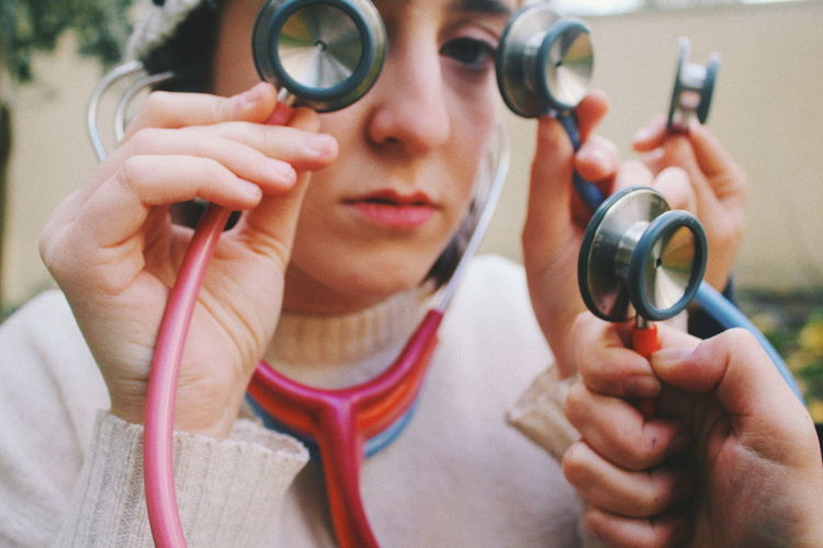 Close-Up Of Woman Holding Stethoscopes Outdoors