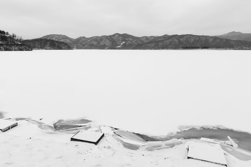 black and white image of snow-covered lake, Uiamho Lake in Chuncheon, Gangwondo, South Korea Black & White ChunCheon Cold Lake Cold Weather Gongjicheon Snow Land Uiamho Lake Winter Winter Landscape Beauty In Nature Black And White Blackandwhite Bw Cold Cold Temperature Day Lake Landscape Mountain Mountain Range Nature No People Outdoors Salt - Mineral Scenics Sky Snow Snow-covered Snow-covered Lake Tranquility Weather Winter Winter Lake Winter Land Winter Time