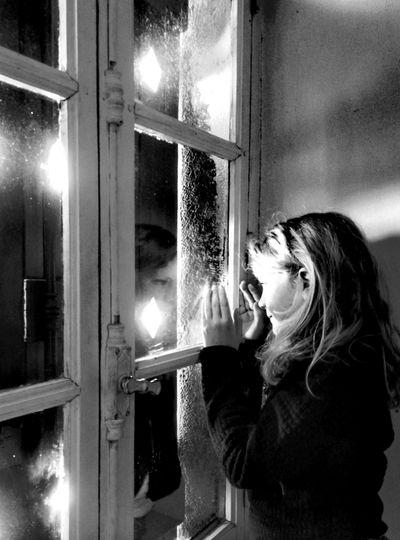 Girl looking away through window against wall