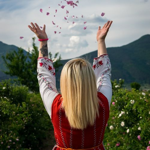Rear view of woman throwing petals against sky