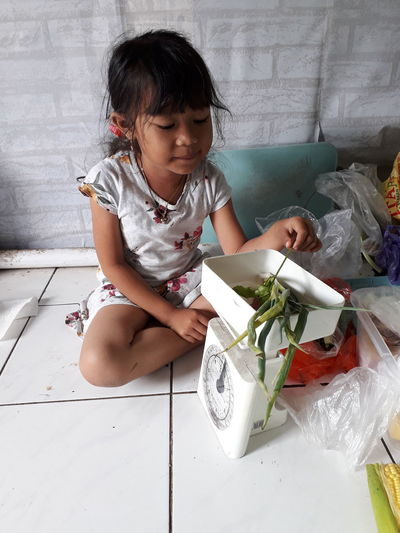 Cute girl weighing vegetables while sitting at home