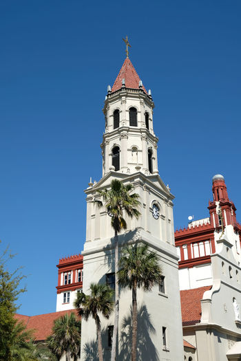 Bell tower and front entrance to the Cathedral Basilica of St. Augustine in St Augustine, Florida. Blue skies and palm trees. Spanish Mission and Neoclassical architecture. No clouds. Architecture Bell Tower Building Exterior Built Structure Cathedral Basilica Of St Augustine Church Church Architecture Churches Day No People Outdoors Religious Architecture Sky Spanish Mission St Augustine St Augustine Florida St Augustine, FL