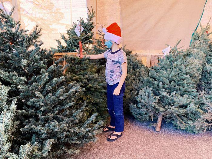 Full length of girl standing by christmas tree