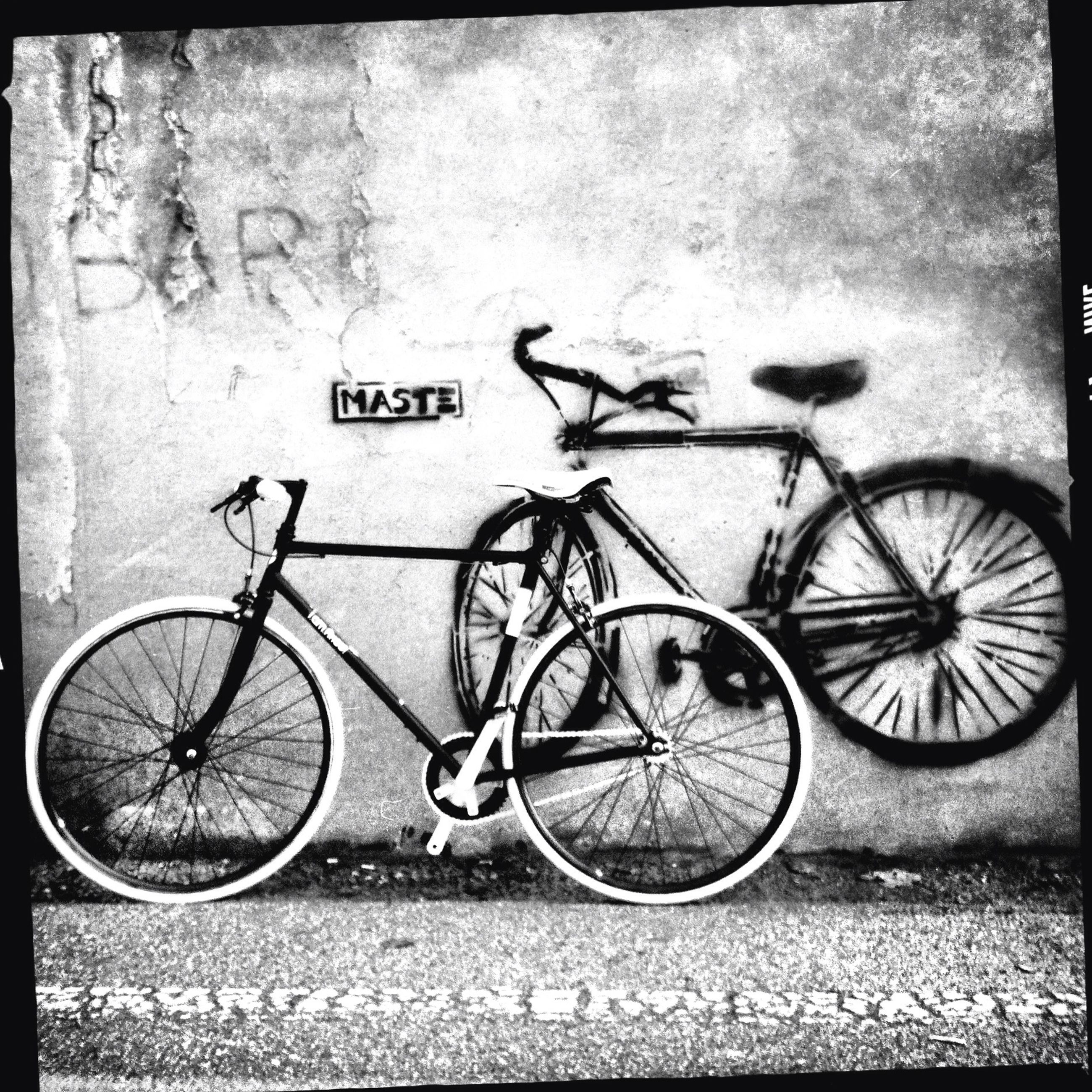 bicycle, transportation, mode of transport, land vehicle, text, stationary, wall - building feature, parking, parked, transfer print, western script, auto post production filter, communication, wall, street, wheel, graffiti, outdoors, day, no people