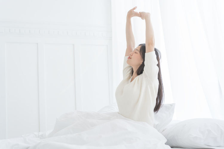 Young Asian woman in the morning she stretching in her bed in the bedroom Wake Wake Up Wakeup Awake Awakening Morning Lazy Stretching Stretch Asian Girl Asian  Woman Female Lady Girl Bedroom Bed One Person Lifestyles Young Adult Women Furniture Indoors  Young Women Arms Raised Human Arm Adult Domestic Room Home Interior Waist Up Real People Relaxation White Color Sheet Hairstyle Beautiful Woman Human Limb