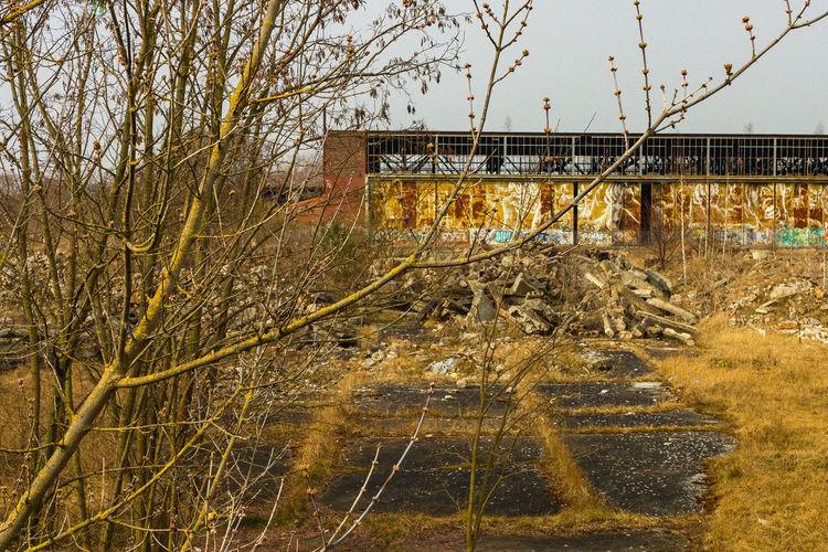 Abandoned bridge amidst trees on field against sky