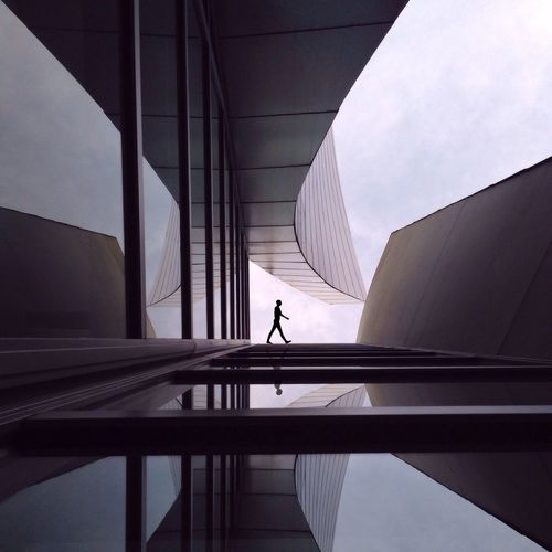 Silhouette Person Walking Outside Modern Building