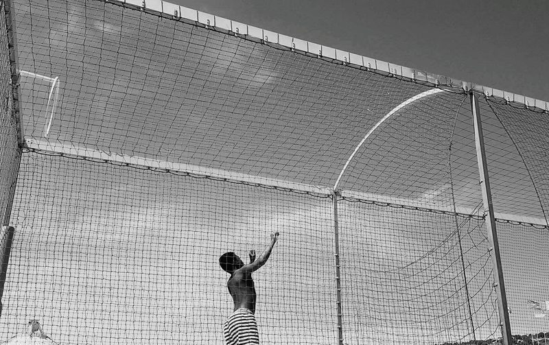 Low angle view of shirtless man standing amidst net against sky