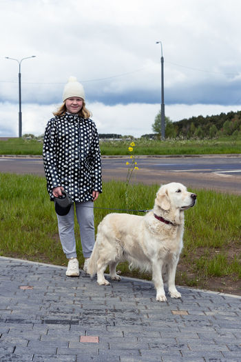 Portrait of woman with dog standing against wall