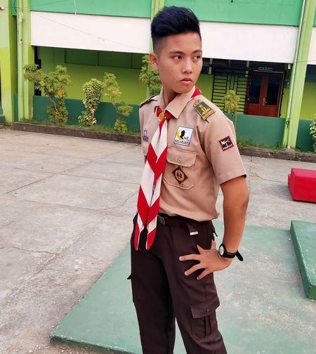 Boy wearing uniform standing against building