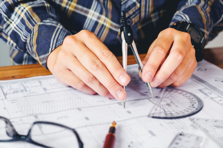 Cropped hands of architect working at table