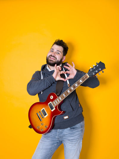 Guitar Electric Man Hair Beard Black Musician Playing Musical Instrument Hoodie Singing Singer  Entertainer Single Solo Entertainer Star Artist Art Profession Model Portrait Pose Jeans Yellow Orange Copy Space Fun Happy Lifestyle Learn Funny Solo Rock Guitar Valuable Band Sheet Music Song Music Rehearsal Modern Cool Three Quarter Length String Instrument One Person Young Adult Front View Holding Musical Equipment Casual Clothing Arts Culture And Entertainment Smiling Indoors  Standing Young Men Colored Background Skill