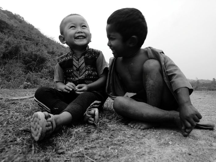 Close-up of cheerful boys sitting on field