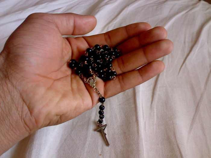 Person Holding Rosary Beads