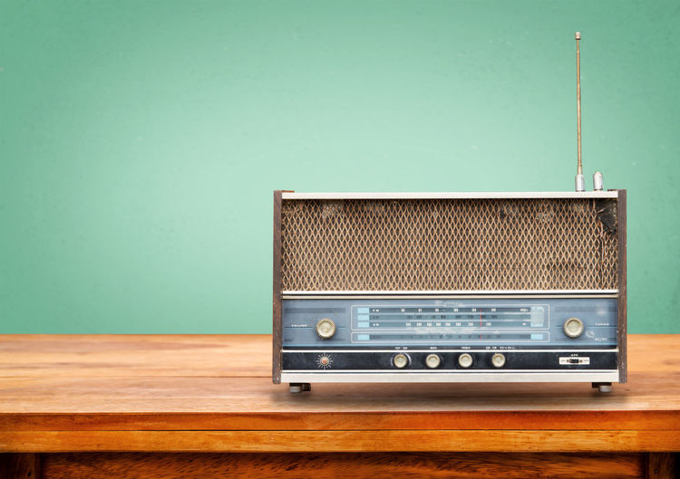 Close-up of radio on wooden table against green background