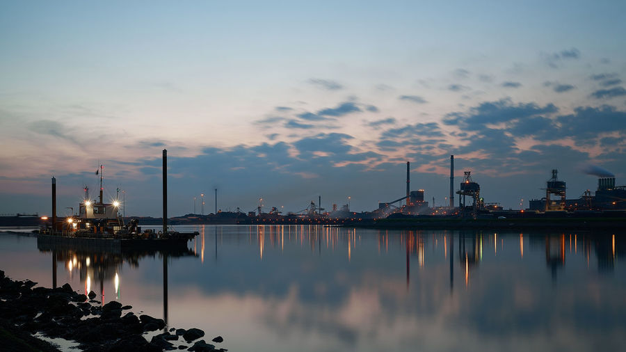 Harbor In River By Industrial District Against Cloudy Sky During Sunset